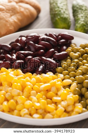Sweet corn, beans and peas in a white plate with bread and cucumber on a wooden table, closeup, selective focus, vertical - stock photo