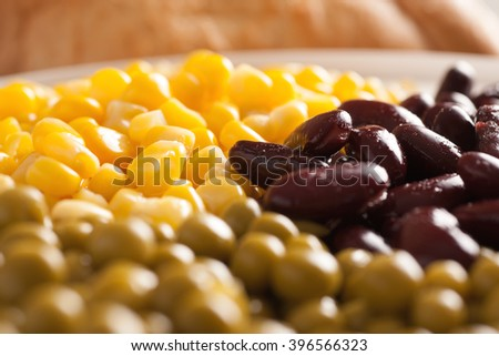 Sweet corn, red beans and green peas in a white plate with bread, selective focus, closeup macro shot - stock photo