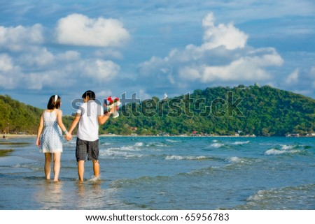 sweet couples walking by hand in hand along the beach with gentle ripple - stock photo