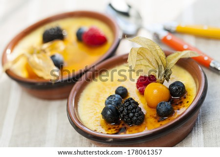 Sweet creme brulee desserts topped with fresh berries - stock photo