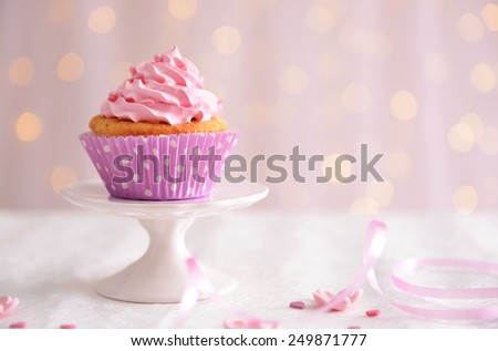 Sweet cupcake on table on light background - stock photo