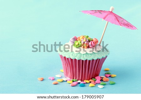 sweet cupcakes decorated with sugar paste and cream - stock photo