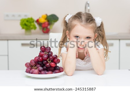 Sweet cute young girl with two ponytails refuses to eat the fresh grapes. - stock photo
