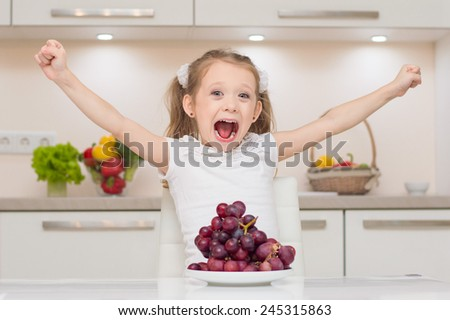 Sweet cute young positive girl with two ponytails shouts and put hands up near bowl full of fresh grapes. - stock photo