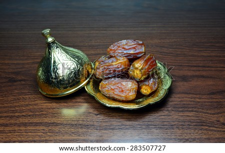 sweet dates in bowl on a wooden table - stock photo