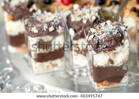 Sweet Dessert. Chocolate, nuts and berry pudding in small plastic cups. - stock photo