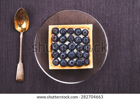 Sweet dessert with blueberries on transparent saucer with spoon vintage - stock photo