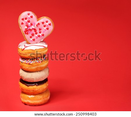 Sweet donuts with heart shaped donut on the top over red background - stock photo