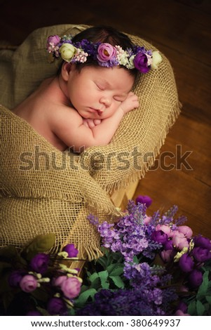 Sweet dreams of newborn baby. Beautiful little girl with lilac flowers - stock photo