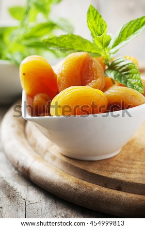 Sweet dried apricots and mint on the wooden table, selective focus - stock photo