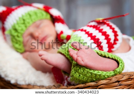 Sweet Feet.  Adorable newborn wearing a red and white striped hat and leggings.  Focus on foot in the foreground.   - stock photo