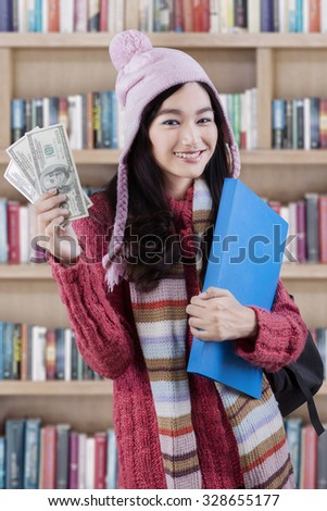 Sweet female student standing in the library while wearing winter clothing and holding money dollars - stock photo