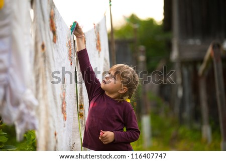 Sweet five-year girl with the clothesline outdoor - stock photo