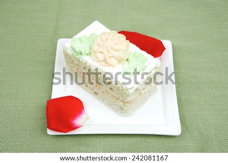 sweet food: cake with whipped cream served with roses on white saucer - stock photo