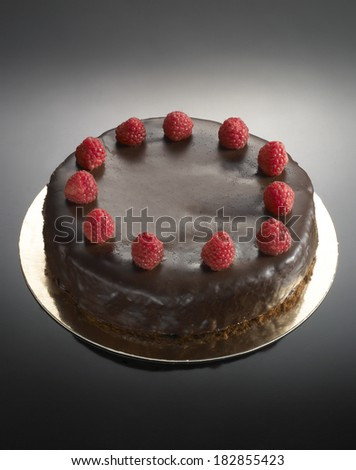 sweet food dessert, chocolate cake with strawberries, on a glossy black background - stock photo