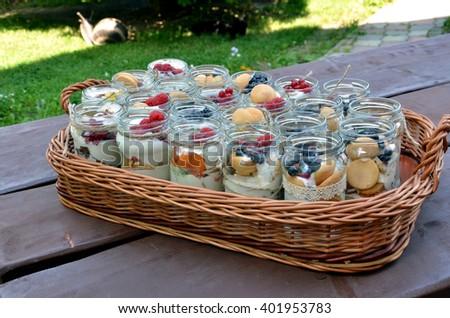 Sweet, fresh and healthy fruit dessert in many bottling jars in wicker basket  - stock photo