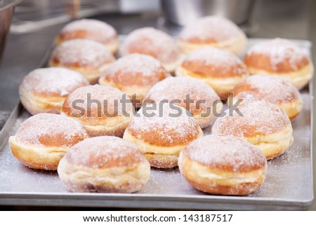 Sweet fried pastry on baking sheet in bakery - stock photo
