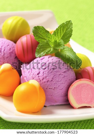Sweet fruit pralines with scoops of assorted ice cream on a rectangular plate - stock photo