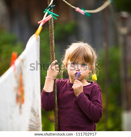 Sweet funny girl with clothespin and the clothesline. - stock photo