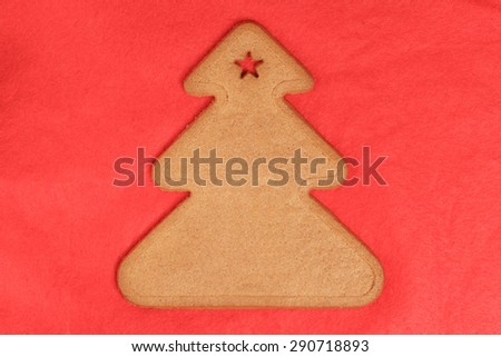 Sweet gingerbread cookie shaped like a Christmas tree on red cloth background. Sweet Xmas treat - stock photo