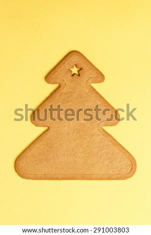 Sweet gingerbread cookie shaped like a Christmas tree on yellow. Sweet Xmas treat - stock photo