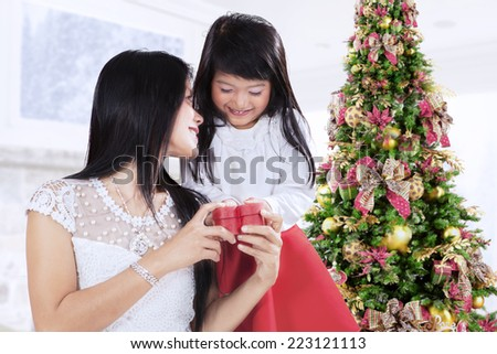 Sweet girl giving present to her mother at home in christmas day - stock photo