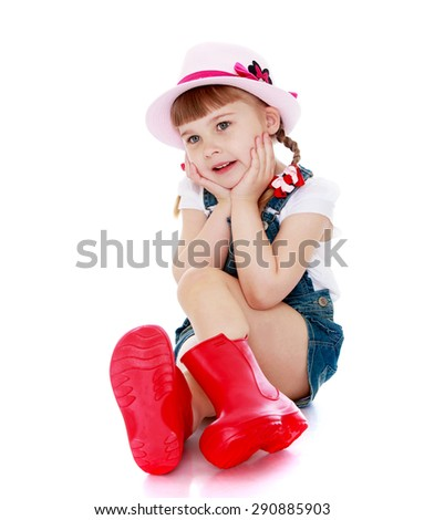 Sweet girl in red rubber boots and short shorts sitting on the floor my head in my hands - isolated on white background - stock photo