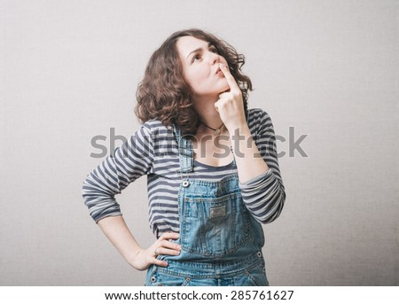 sweet girl remembers something dressed in overalls - stock photo
