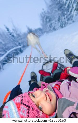 Sweet girl riding on reindeer. Ruka, Finland - stock photo