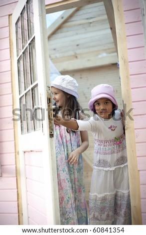 Sweet girlfriends open the door of him little house - stock photo