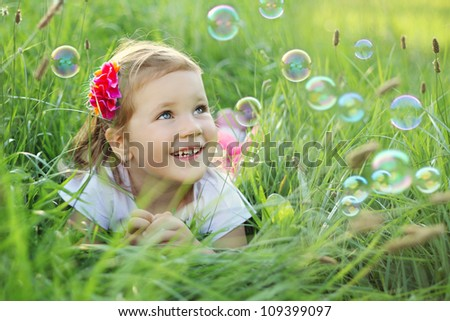 Sweet, happy, smiling three year old girl laying on a grass in a park playing with bubbles - stock photo
