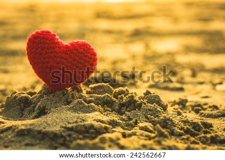 sweet heart on sand beach under sunset and warm light. abstract background love summer on the beach.  - stock photo