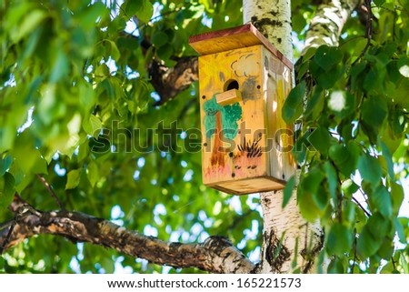 Sweet Home. A closeup view of a birdhouse on a birch tree in summertime. The box is painted by child's hand. - stock photo