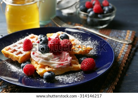 Sweet homemade waffles with forest berries and cream on plate, on dark wooden background - stock photo