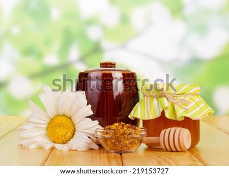 Sweet honey in jar on green background - stock photo