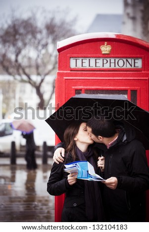 Sweet honeymoon couple kissing instead of consulting map in London - stock photo