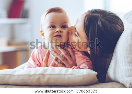 Sweet kiss from mommy. Close-up of beautiful young woman holding baby girl in her hands and kissing her with love while sitting on the couch at home - stock photo