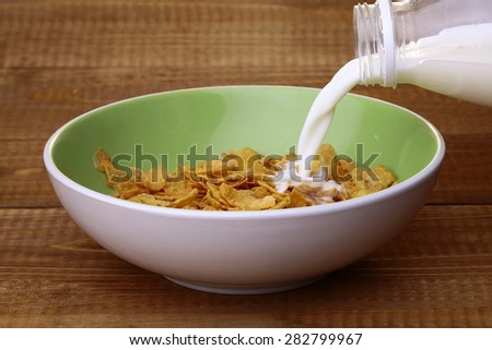 Sweet krispy of cereal cornflakes with frosting in light green plate and spoon filling in with milk from plastic bottle on brown wooden table top background, horizontal photo - stock photo