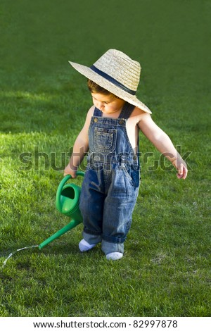 sweet little baby gardener caught in the moment while working hard in his garden whith his big hat on - stock photo