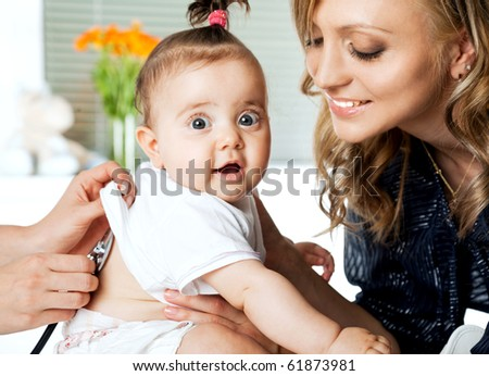 Sweet little baby girl in hospital being examinated and held by mother - stock photo