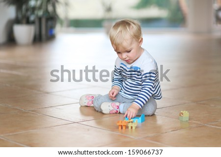 Sweet little baby girl play with plastic bricks sitting indoors on a tiles floor - stock photo