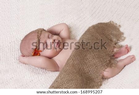 Sweet little baby girl wearing a burlap blanket and headband with orange flower.  - stock photo