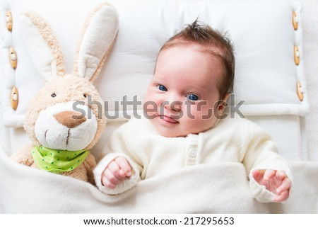 Sweet little baby girl with a toy bunny in bed - stock photo