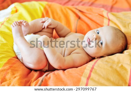 sweet little baby playing with her legs - stock photo