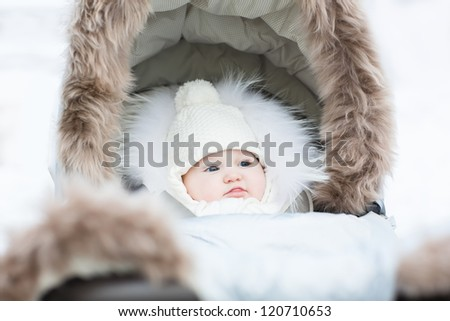 Sweet little baby sitting in a winter fur stroller on a snowy day - stock photo