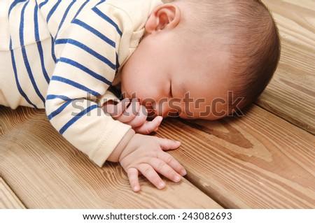 sweet little baby sleep on wooden floor  - stock photo