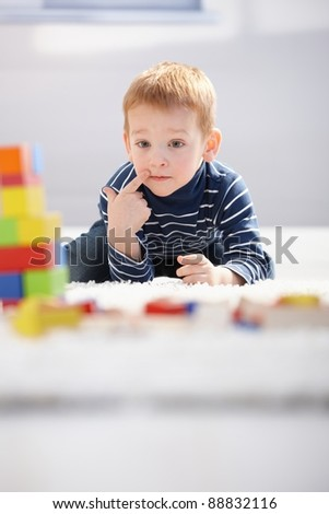 Sweet little boy laying on floor, playing with building cubes, thinking.? - stock photo