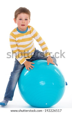 Sweet little boy sitting on a big blue ball, isolated on white background - stock photo