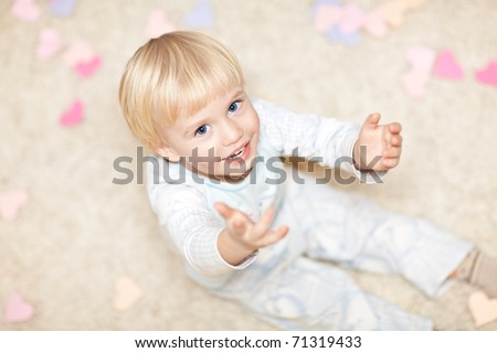 Sweet little boy sitting on the floor in pajamas and stretching his hands. There are little heart shapes around him. - stock photo