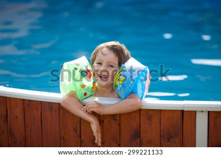 Sweet little boy, swimming in big swimming pool, summertime - stock photo